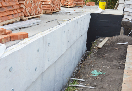 Insulating Exterior Foundation Walls. Foundation Waterproofing and Damp proofing Coatings. Waterproofing house foundation with spray on tar with insulation styrofoam sheets for House Energy Saving.