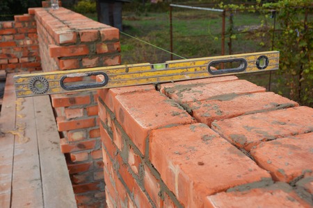 Bricklaying with Spirit Level to Check New Red Brick House Wall Outdoor. Basic Bricklaying on House Construction Site