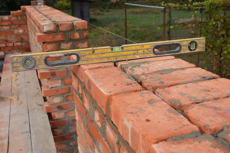 Metselen met waterpas om nieuwe rode bakstenen huismuur buiten te controleren. Basis metselen op de bouwplaats van het huis