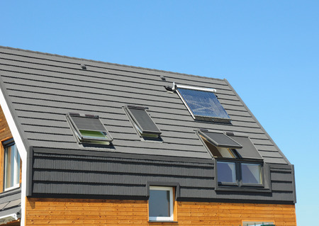 太陽電池パネルおよびエネルギー効率の天窓とドーマ屋外モダンな家の屋根にソーラー温水器。