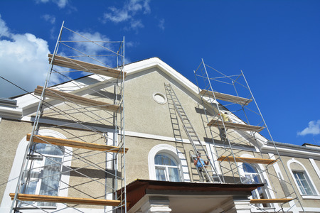 Painting and Plastering Exterior House Scaffolding Wall. Home Facade Insulation, Sctucco and Painting Works During Exterior Wall  Renovations and Repair. Builder Worker Plastering House Facade Outdoor