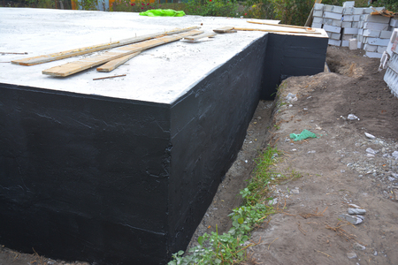 Waterproofing foundation bitumen. Foundation Waterproofing, Damp proofing Coatings.Waterproofing house foundation with spray on tar. Construction techniques for waterproofing basement and foundations