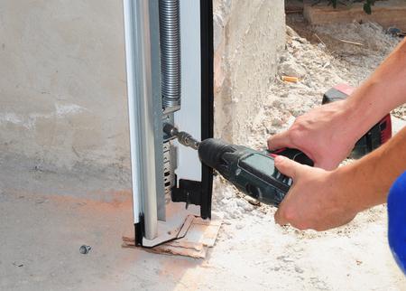 Constructor installeren en repareren garagedeur. Reparatie, isolerende garagedeur. Garagedeurafdichting, garagedeurveren, garagedeurvervanging, garagedeurreparatie.