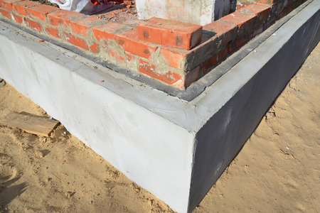 Foundation Insulation with bitumen waterproofing membrane brick wall to avoid dampness. Bricklaying, Brickwork, Building Brick House Wall.