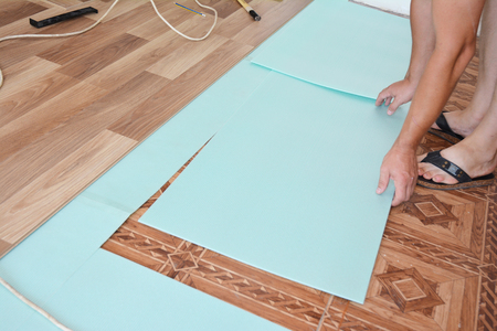 Worker laying laminate flooring. Step by Step.