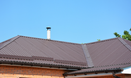 Metal roofing construction with gutter system and asbestos chimney Stock Photo