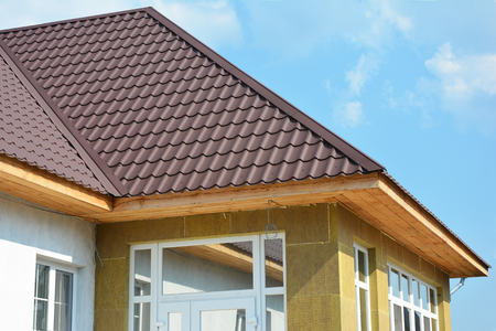 Roofing Construction. House wall repair, renovation, insulation detail. Building insulation exterior, added to buildings for comfort and energy efficiency. Rain Gutter. Soffit and Fascia installation.