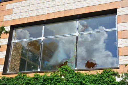 曇り空を反映した割れたガラス窓。避難者の屋外で壊れた窓枠を持つ家の窓。
