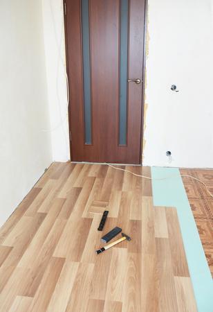 단열 및 방음 시트가있는 목재 라미네이트 바닥 설치. 내부.