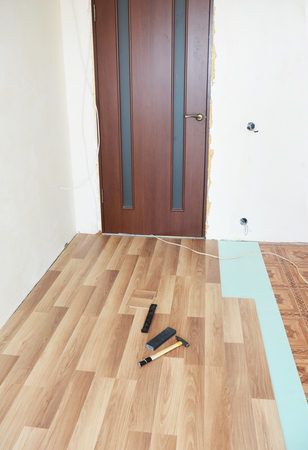 Installing wooden laminate flooring with insulation and soundproofing sheets. Interior. Imagens