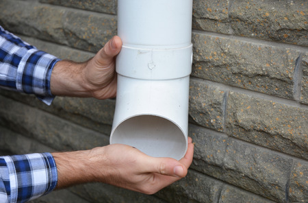 Rain Gutter Downspouts & Downpipes Installation with Contractor Hands. Cleaning and Repair. Archivio Fotografico