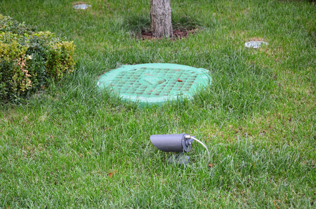 Manhole Sewer Cover with Garden Light, Lanterns In Lawn.  Solar Powered Lamp in the garden Archivio Fotografico