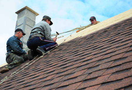 KIEV - UKRAINE, October - 09, 2017: Roofing Construction. Roofing Contractors Install New House Roofing with Asphalt Shingles Roofing Construction. Roofers with safety rope. Roofing Contractor. Archivio Fotografico