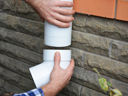 Man installing plastic rain gutter system pipeline. Guttering, Gutters, Plastic Guttering, Guttering & Drainage by Handyman hands. Guttering Down pipe Fittings.
