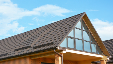 屋根裏部屋の天窓の窓の壁。雪から雨溝システムと屋根保護が金属屋根のモダンな住宅建築。