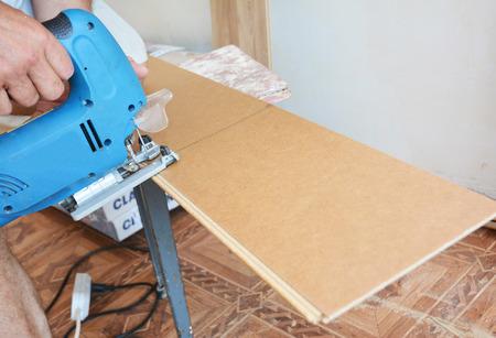 라미네이트 바닥재를 세로로 자른다. 핸드 톱으로 라미네이트 바닥을 자르십시오.