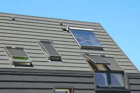 Modern huisdak met zonneboiler, zonnepanelen en dakramen, mooi nieuw modern huis met zonnepanelen. Open dakramen op zolder. Stockfoto