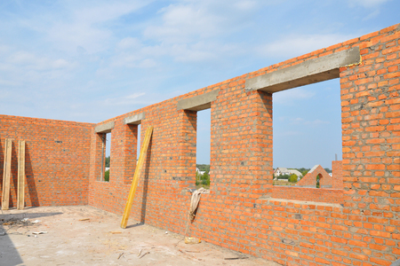 Unfinished Red Brick House Wall  under Construction without Roofing.  Attic Windows Concrete Lintel Frame Construction. House construction site. Brickwork. Stock Photo