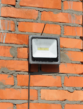 LED flood light, spot light on the top house construction site outdoor. Waterproof  LED Floodlights Or Lawn Lighting on the Construction Site. Stock Photo - 87710471