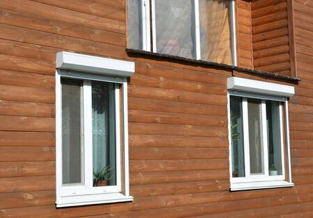Windows with rolling shutter protection on the wooden house facade exterior