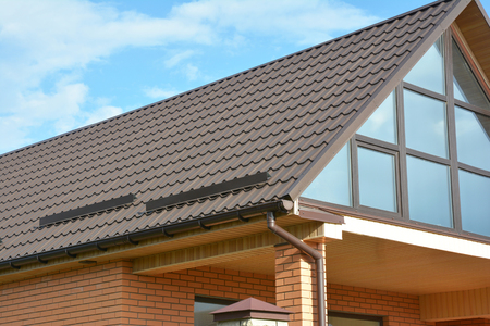 Building Modern House Construction with metal roof, rain gutter system and roof protection from snow, snow bar (Snow guard). Roof Snow Guards: Building Materials & Supplies. Attic skylight window. Standard-Bild
