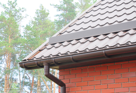 雨樋のパイプラインシステムのインストール。屋根の建設。雪 (スノーガード) からの雨樋システムと屋根の保護。ホーム雨樋、側溝、雨樋 & 排水管 写真素材