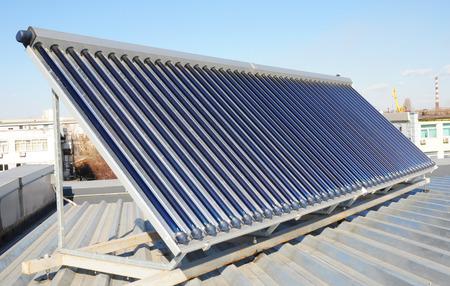 Dak met energiebesparing en energie-efficiëntie. Metalen dakconstructie met zonnepanelen en zonneboiler (SWH) systeem. Passief huis. Eco-huis of eco-huis.