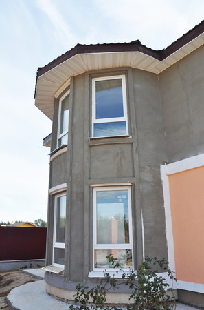 Unfinished house with plastering wall and stucco wall after mineral wool wall insulation. Painting wall. Soffit roof construction.