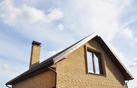 Attic construction outdoors. Roofing Construction with brick chimney and roof gutters system. Mansard roof.  Stock Photo