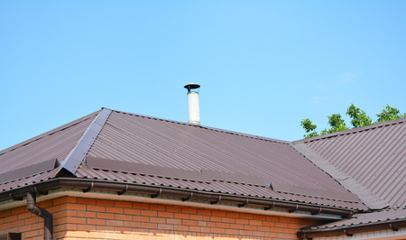 Metal roofing construction. Roof Repair with Rain Gutter and Problem Areas for House Metal Corner Roofing Construction Waterproofing.  Stock Photo