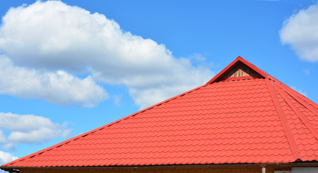 Red metal roofing construction. Metal sheets house roof. Roofing Construction. Stock Photo