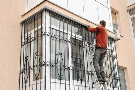 KIEV, UCRÂNIA - MAIO, 15, 2017: O trabalhador instala barras de segurança do ferro da janela para a segurança da casa. Contratante que instala barras de segurança do ferro da janela com soldadura. Segurança Grades Shutters Instalação. Editorial