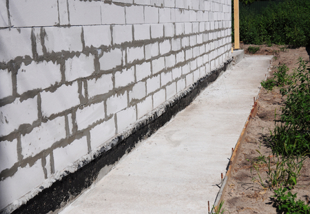 Waterproofing and insulation unfinished house foundation wall. Waterproofing house foundation with bitumen membrane.