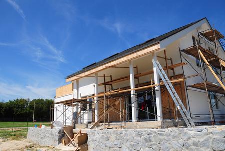 Renoveren en repareren gevel van woonhuizen gevel met minerale wol isolatie, pleisterwerk, schilderij muur buitenshuis. Het remodelleren van Huisbouw met asfalt dakspanen dak. Huis renovatie.