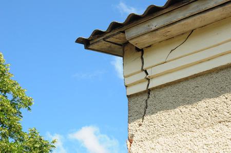 El detalle de la arquitectura de la esquina dañada de la casa dilapidó la pared vieja de la fachada del edificio. Reparación de techo