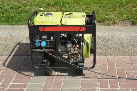 Diesel Portable Generator. Close up on Mobile Diesel Backup Generator. Diesel   Standby Generator - Outdoor Power Equipment. Stock Photo