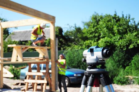 Surveying measuring equipment level transit on tripod at contractors and construction building area site.Theodolite or Tacheometer. Stock Photo