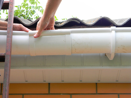 Contractor Installing rain gutter system on the roof.  Stock Photo