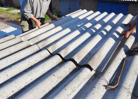 Asbestos Removal. House asbestos roof repair with roofer hands. Roofers Roofing Construction and Roof Repair.