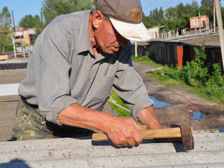 KIYV, UKRAINE - JUNE, 6, 2017: Roofer repair asbestos roof with hammer. Old contractor roofing construction. Editorial