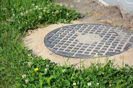 Manhole cover installation in the garden. Stock Photo