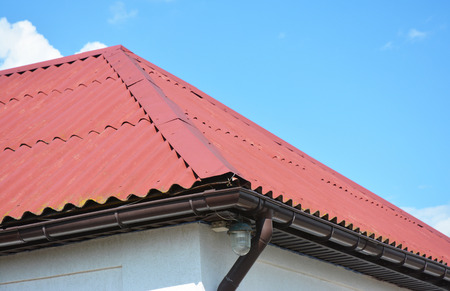 Close up on red roofing construction house with roof gutter system. Stock Photo