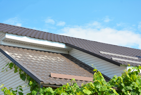 Close up on Metal Roofing Construction Problem Areas. Gable and Valley type of roof construction with Plastic Soffit and Fascia