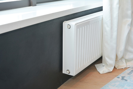 White radiator heating with thermostat for energy saving.