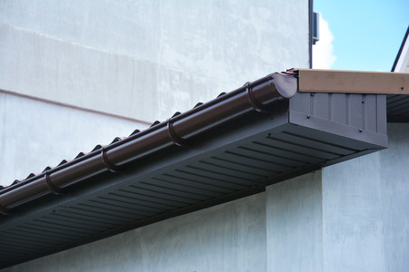 Close up on house plastic roof gutter with soffit and fascia board. Stock Photo