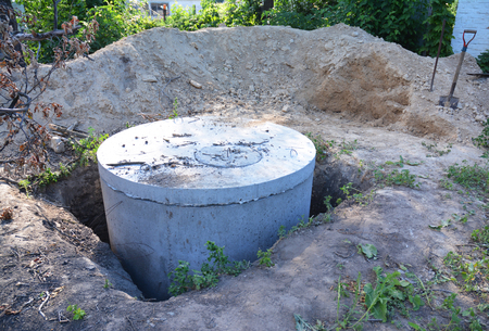 Manhole cover installation with sewer tank outdoors.