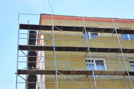 Aislamiento térmico de la pared de la casa exterior con lana mineral, edificio en construcción. El aislamiento se define como un material o combinación de materiales que retardan el flujo de calor. Foto de archivo - 91605938