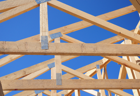 Wooden Roof Frame House Construction. Close up on wooden beam and rafters Stock Photo