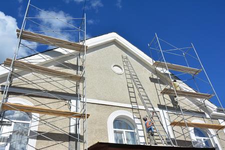 Schilderen en bepleisteren exterieur huis steigers muur. Gevelisolatie en schilderwerkzaamheden aan huis tijdens exterieurrenovaties. Bouwer werknemer stukadoors gevel.