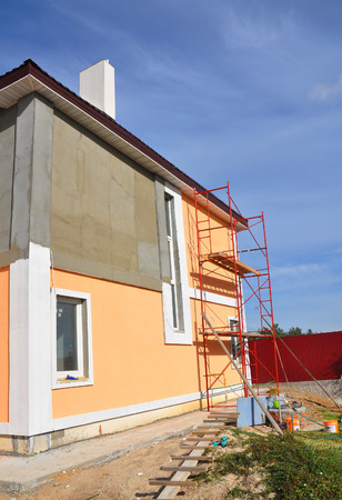 Close up on painting house wall. Construction or repair of the rural house with, eaves, windows, chimney, fixing facade, insulation, plastering and painting outdoor. House facade construction